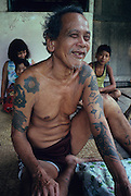 DAYAK TATTOOS, MALAYSIA. Sarawak, Borneo, South East Asia. Dayak, 'Iban', man with tattoos, longhouse verandah. Tropical rainforest and one of the world's richest, oldest eco-systems, flora and fauna, under threat from development, logging and deforestation. Home to indigenous Dayak native tribal peoples, farming by slash and burn cultivation, fishing and hunting wild boar. Home to the Penan, traditional nomadic hunter-gatherers, of whom only one thousand survive, eating roots, and hunting wild animals with blowpipes. Animists, Christians, they still practice traditional medicine from herbs and plants. Native people have mounted protests and blockades against logging concessions, many have been arrested and imprisoned.