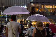A western couple with umbrellas take in the sights of Shibuya Crossing in Shibuya, Tokyo, Japan. Friday, July 15th 2016
