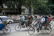 Dhaka, Bangladesh - November 1, 2017: Bicycle rickshaws travel down a street in Dhaka, Bangladesh. One passenger travels with a suitcase, and a smile on his face.