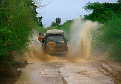 Leisure - 4x4 driving, offroad driving, adventure, a 4x4 vehicle drives through a mud puddle of water with a man hanging out of the car, dare-devil, fun, rain, puddle of water, offroad adventure in Angola