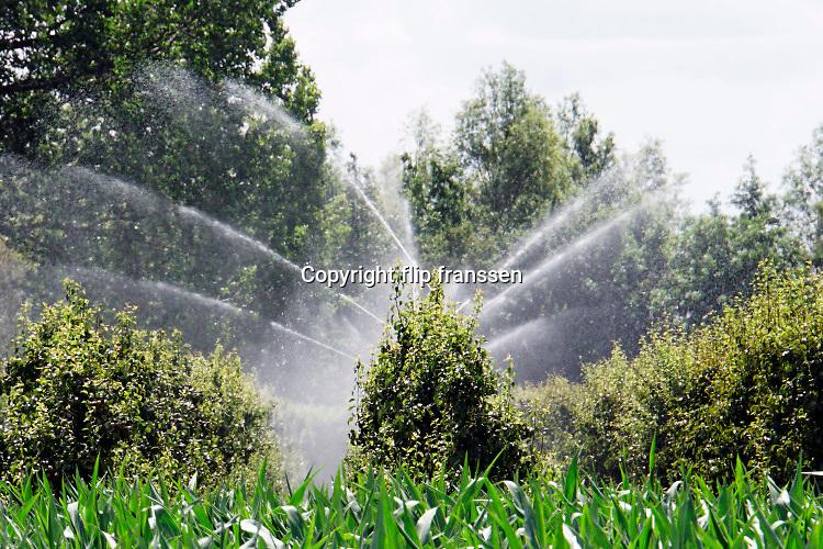 Nederland, Deest, 2-7-2019Een fruitteler beregent zijn boomgaard nat dmv sproeiers, watersproeiers.Foto: Flip Franssen