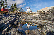 A unique landscape of beautifully striped bedrock descends from Pemaquid Light to the Atlantic Ocean. Pemaquid Point Lighthouse was built in 1835 and commemorated on Maine's state quarter (released 2003). Visit Lighthouse Park at the tip of Pemaquid Neck in New Harbor, near Bristol, Lincoln County, Maine, USA. From Damariscotta on bustling US Highway 1, drive 15 miles south on Maine Route 130 to the park. The keeper's house (built 1857) is now the Fishermen's Museum at Pemaquid. Geologic history: Silurian Period sediments laid down 430 million years ago were metamorphosed underground into a gneiss 360-415 million years ago, and intruded by molten rock which cooled slowly, creating the park's exposed metamorphic gray rocks with dikes of harder, white igneous rock. Underground heat and pressure tortured and folded the rock layers into the striking patterns that are now pounded and polished by the sea and rough weather.
