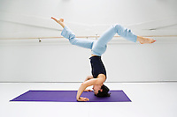 Young woman doing a headstand on a yoga mat in a white room.