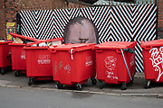 Street art graffiti of a bald head peeks over some red recycling bins in Digberth, Birmingham, United Kingdom. Digbeth is an area of Central Birmingham, England. Following the destruction of the Inner Ring Road, Digbeth is now considered a district within Birmingham City Centre. As part of the Big City Plan, Digbeth is undergoing a large redevelopment scheme that will regenerate the old industrial buildings into apartments, retail premises, offices and arts facilities. There is still however much industrial activity in the south of the area.