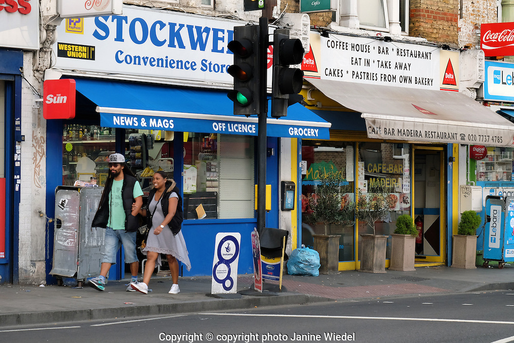 Couple in street passing Shops and restaurant in Stockwell South London