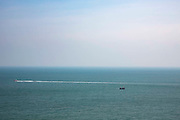 Two boats sail in opposite directions in the calm waters of The English Channel photographed from Folkestone, Kent, England, United Kingdom.