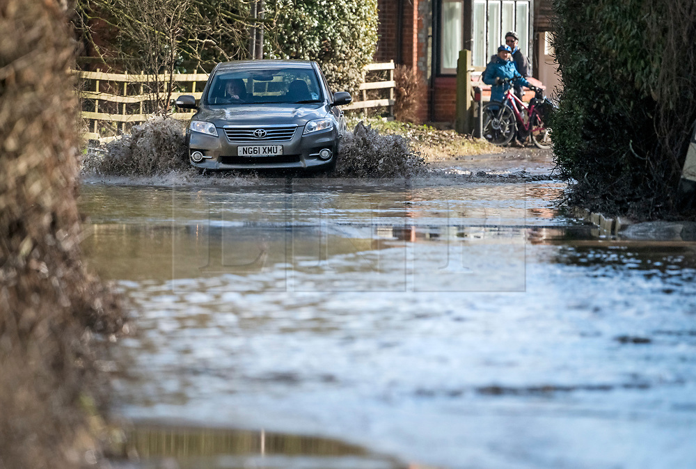 © Licensed to London News Pictures. 05/02/2021. Sonning, UK. A car ploughs through flood water in the village of Sonning in Berkshire, where the River Thames has broken its banks.  Large parts of the UK experience more wet conditions which is expected to bring further flooding. Photo credit: Ben Cawthra/LNP
