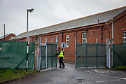A security guard opens the only entrance to access Napier Barracks on the 12th of January 2021, Folkestone United Kingdom. Over 400 asylum seekers are being kept at Napier Barracks in unsuitable, cold accommodation, they are experiencing mental health issues as well as being vulnerable to health conditions including COVID-19.