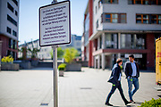 A warning sign explaining social distance on a square where are not more then 2 people allowed to meet infront of a shopping center in Bad Homburg which is a spa city close to the Taunus mountain range.