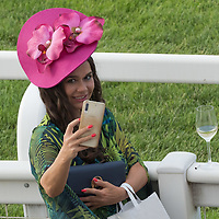 Woman wearing a hat takes a selfie at a hat fashion contest held at Hungarian horse race derby in Budapest, Hungary on July 4, 2021. ATTILA VOLGYI