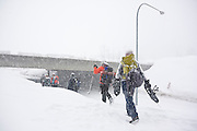 A group of snowshoers walk out onto the road carrying their snowshoes at Snoqualmie Pass, Washington.