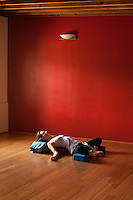 """Yoga photography featuring the practice of restorative yoga postures utilizing bolsters, blankets, blocks, and a chair.<br /> :::<br /> """"Our yoga practice—at least the styles of yoga that attract the most students—flits from one pose to the next, to the beat of loud music. Staying in a pose is boring and doesn't burn calories, right? But is yoga asana meant to be about burning calories? The yoga sutras define yoga as """"the settling of the mind into silence."""" When we speed along at our habitual pace, our actions become mechanical. Our minds are anywhere but in the present. It is in the present moment where our minds can settle into silence. When we slow down, we can more easily glimpse the silent mind, the infinite sky of awareness.""""<br /> -Charlotte Bell"""