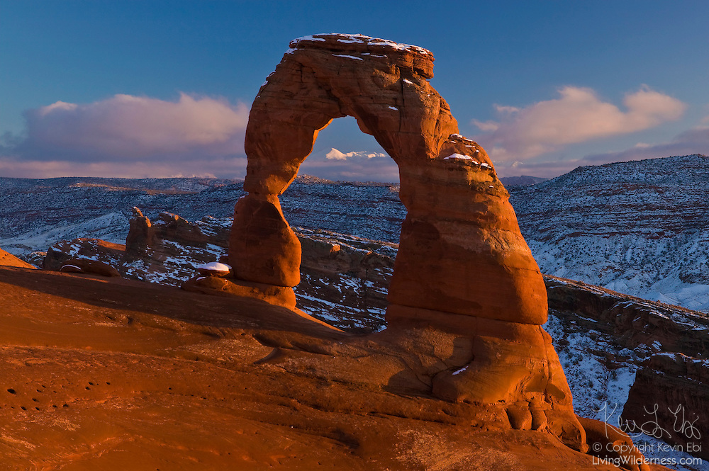 Delicate Arch, dusted in winter snow, frames the La Sal Mountains at sunset. Delicate Arch is a freestanding natural arch located in Arches National Park near Moab, Utah.