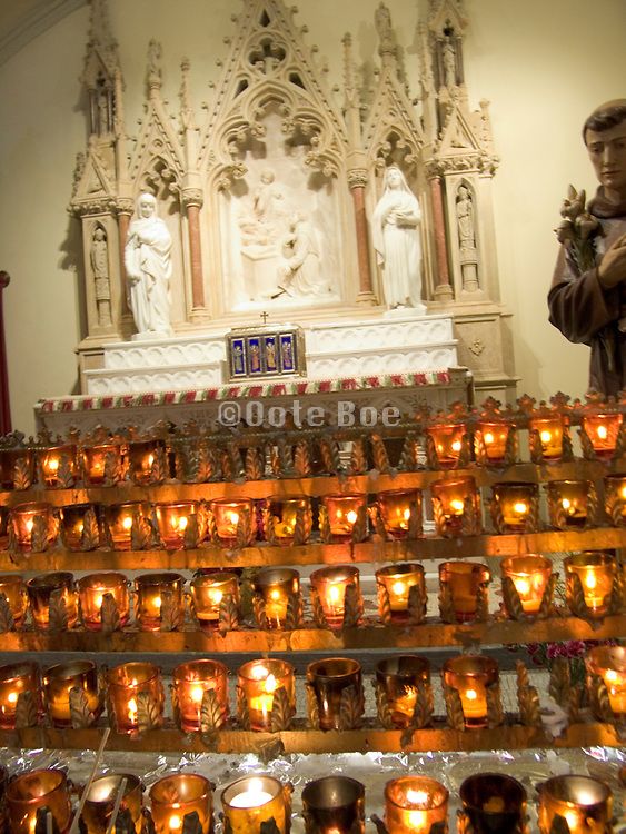 illuminated little votive candles in front of a altar for Saint Anthony of Padua