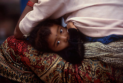 POKHARA, NEPAL - OCTOBER 1992 - A child curls up in her mothers lap at their home in Pokhara, Nepal. (PHOTO © JOCK FISTICK)
