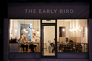 Small business shop front of a new crowdfunded cafe The Early Bird at night in the Kings Heath area of Birmingham, United Kingdom. Kings Heath is a suburb of Birmingham, three miles south of the city centre. It is the next suburb south from Moseley.