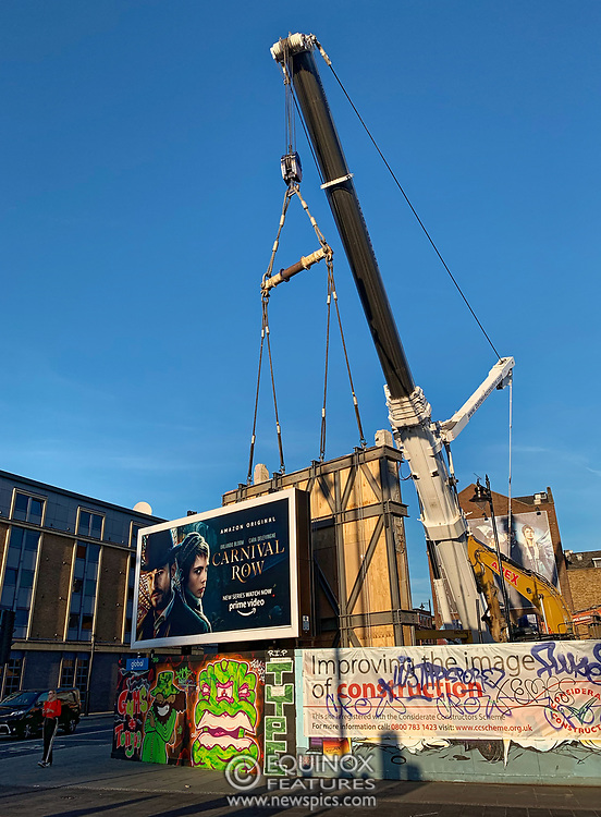 London, United Kingdom - 20 September 2019<br /> EXCLUSIVE SET - Aerial construction specialists and demolition experts use a huge crane to carefully lift intact, a twenty five ton, two-story wall, to preserve a famous Banksy rat image which has been covered up for years. Teams from specialist companies have spent over six weeks cutting around the artwork and fitting custom made eight ton steel supports to enable them to save the historic piece of art. Work has started on the construction of a new twenty seven floor art'otel hotel on the site of the old Foundry building in Shoreditch, east London, and a condition of the planning permission was to preserve the historical Banksy graffiti. A second section of the painting, an image of a TV being thrown through a broken window has already been cut out and moved separately. After the hotel construction is complete the two parts of the Banksy painting will be displayed on the hotel. Our pictures show the stages of work to protect the image, culminating in the lifting of the three story wall by crane. Video footage also available.<br /> Editorial Disclosure: This image is a composite panorama created from a set of images taken within a few seconds of each other.<br /> (photo by: EQUINOXFEATURES.COM)<br /> Picture Data:<br /> Photographer: Equinox Features<br /> Copyright: ©2019 Equinox Licensing Ltd. +443700 780000<br /> Contact: Equinox Features<br /> Date Taken: 20190920<br /> Time Taken: 175741<br /> www.newspics.com