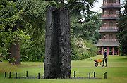 © Licensed to London News Pictures. 07/06/2012. Kew, UK. A gardener walks past 'Black Trunk' created in 2010 from Medium Charred Redwood. The Royal Botanic Gardens, Kew, hosts a photocall for an exhibition of sculpture by David Nash in the grounds and Temperate Houses. The exhibition opens to the public on 9th June 2012 and finishes on 14th April 2013  Photo credit : Stephen Simpson/LNP