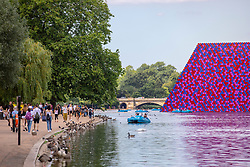 © Licensed to London News Pictures. 23/07/2018. London, UK. People walk past the London Mastaba, a floating sculpture by Christo, in the Serpentine in Hyde Park as hot weather continues in the capital. Forecasters are predicting record temperatures this week. Photo credit: Rob Pinney/LNP
