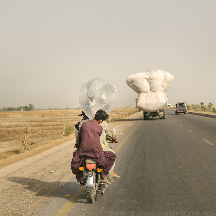 On the outskirt of town, men return from the Jacobabad market after purchasing a large fan.