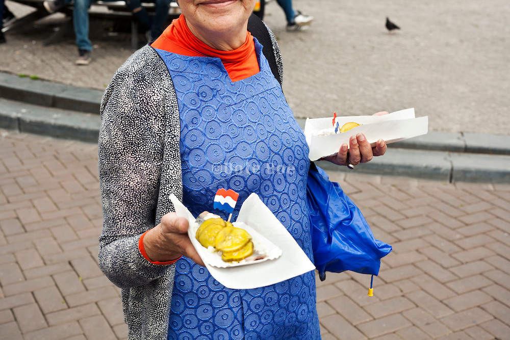 eating RAW herring with pickles in Amsterdam