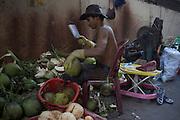 A man opens coconuts in the street, in Phnom penh, Cambodia. PHOTO TIAGO MIRANDA