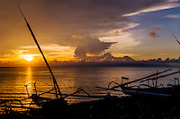 Nusa Tenggara, Lombok, Senggigi. The sun sets in the ocean, in the backgrund you can see Gunung Agung on Bali.