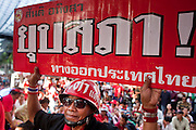 """06 MAY 2010 - BANGKOK, THAILAND: Red Shirt protestors hold up anti-government signs Thursday, May 6. Red Shirt protestors in Ratchaprasong intersection, Thursday May 6, more than one month after the Reds occupied the intersection. Members of the United Front of Democracy Against Dictatorship (UDD), also known as the """"Red Shirts"""" and their supporters moved their anti government protests into central Bangkok Apr. 4 when they occupied Ratchaprasong intersection, the site of Bangkok's fanciest shopping malls and several 5 star hotels. The Red Shirts are demanding the resignation of current Thai Prime Minister Abhisit Vejjajiva and his government. The protest is a continuation of protests the Red Shirts have been holding across Thailand. They support former Prime Minister Thaksin Shinawatra, who was deposed in a coup in 2006 and went into exile rather than go to prison after being convicted on corruption charges. Thaksin is still enormously popular in rural Thailand. This move, away from their traditional protest site in the old part of Bangkok, has gridlocked the center of the city and closed hundreds of stores and restaurants and several religious shrines. On Thursday night the Red Shirt leaders said there has been a """"glitch"""" in the ongoing negotiations to end the standoff. Their opponents, the """"Yellow Shirts"""" who previously supported the incumbent Prime Minister have rejected his peace plan and called for the PM to resign.  PHOTO BY JACK KURTZ"""