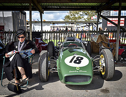 © licensed to London News Pictures. 12/09/2015<br /> Goodwood Revival Weekend, Goodwood, West Sussex. UK.<br /> The Goodwood Revival is the world's largest historic motor racing event. Competitors and enthusiasts dress in period fashions recreating the glorious days of the race circuit.<br /> Pictured A lady in period dress next to a classic Lotus climax.<br /> <br /> Photo credit : Ian Whittaker/LNP