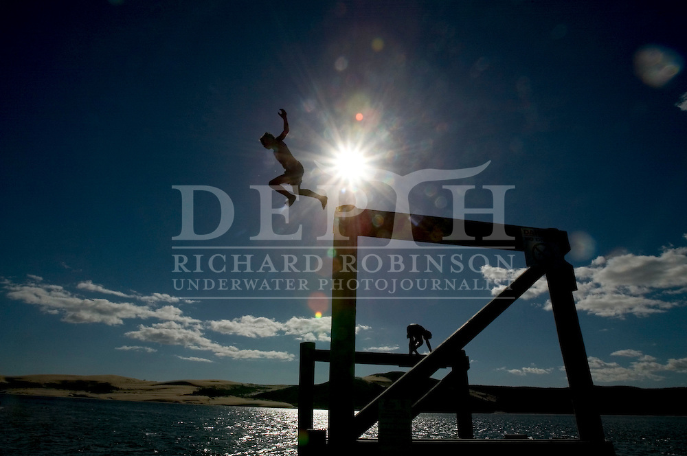 12-year-old Levi Parsons jumps of the Opononi wharf into the Hokianga Harbour, New Zealand. November 2005.<br /> Photograph Richard Robinson.<br /> 2005 © New Zealand Herald A Division of APN New Zealand Ltd.<br /> No Reproduction without prior written permission. Contact www.newspix.co.nz to licence photograph.