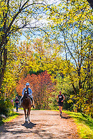 Horseback rider and joggers on the Highline Canal path on an autumn afternoon, Littleton, Colorado USA.