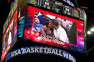 """U.S. President Barack Obama and first lady Michelle Obama are shown kissing on the """"Kiss Cam"""" screen during a time out in an Olympic basketball exhibition game between the U.S. and Brazil national men's teams in Washington. They had been booed playfully by fans for not kissing earlier in the evening."""
