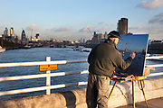 Artist paints the river Thames and City of London from an easel placed on Waterloo Bridge. As the evening light fades he captures the light beautifully.