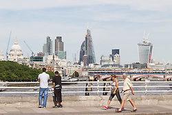 © Licensed to London News Pictures. 15/07/2013. London, UK. As meteorologists predict the current heatwave will continue into August visitors to London's Waterloo Bridge take in views across the city today (15/07/2013). Photo credit: Matt Cetti-Roberts/LNP
