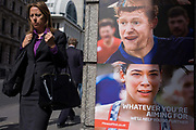 A businesswoman walks past a poster ad for City of London Fitness First gyms. Dressed in a formal dark suit and carrying a handbag, the lady walks down Bishopsgate past the small wall poster that tries to attract new business from city workers wanting a healthier lifestyle. The faces of young people seen in a moment of exertion, taking part in sport is to the woman's right with a strapline using the key marketing words Aim, Help and Further.