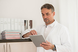 Male doctor using digital tablet in clinic, Munich, Bavaria, Germany