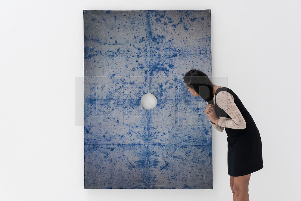 """© Licensed to London News Pictures. 22/06/2016. London, UK. A staff member looks at """"The Guild"""" by Anna Hughes at the annual exhibition of works by artists graduating from the UK's longest established art school, RA Schools Show, at the Royal Academy in Piccadilly.  Works from 17 emerging artists are on show 23 June to 3 July. Photo credit : Stephen Chung/LNP"""