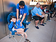 14 OCTOBER 2011 - SCOTTSDALE, AZ:   An Apple Store employee talks to HILLARY CLARK, 9, before the iPhone 4S went on sale at the Apple Store in Scottsdale Quarter. Hillary was with her father, they arrived at the Apple Store at 9:30PM Thursday and spent the night camped with others who wanted to be the first to get their hands on the new iPhone. Hundreds of people lined up at the Apple Store in the Scottsdale Quarter in Scottsdale, AZ, Friday, Oct. 14, to buy the iPhone 4S. The phone sold out in pre-orders last week and sales at the Scottsdale Apple Store were brisk through the morning.     PHOTO BY JACK KURTZ