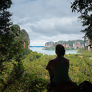 Silhouette of a girl sitting high on a rock meditating and observing the view of Railay beach in Krabi, Thailand