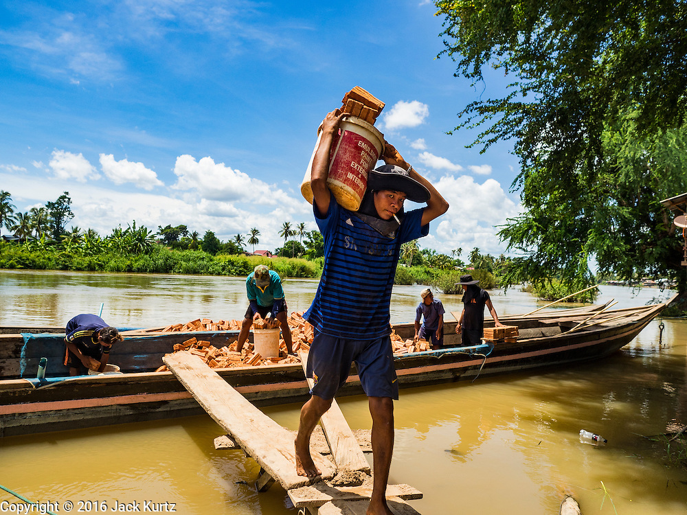 19 JUNE 2016 - DON KHONE, CHAMPASAK, LAOS:  A laborer unloads bricks brought to Don Khone Island from the Lao mainland. Don Khone Island, one of the larger islands in the 4,000 Islands chain on the Mekong River in southern Laos. The island has become a backpacker hot spot, there are lots of guest houses and small restaurants on the north end of the island.     PHOTO BY JACK KURTZ
