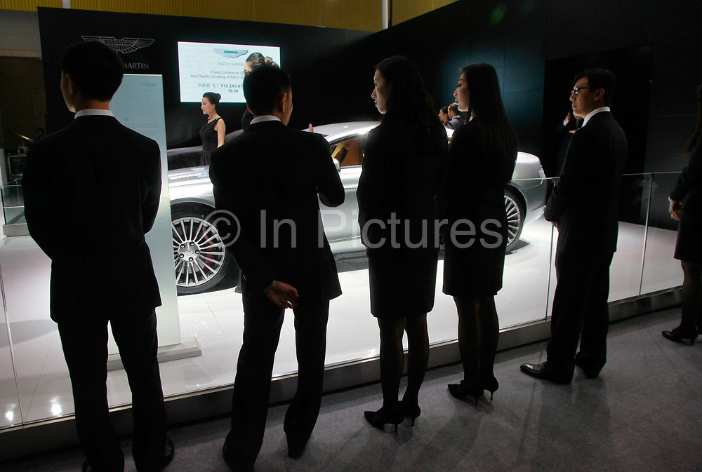 Visitors look at the Aston Martin display area during the China ( Guangzhou) International Automobile Exhibition in Guangzhou, Guangdong Province, China, on Monday, Nov. 21, 2011. Despite signs of slowing, China remains the largest and fastest growing market for international car makers, especially in the luxury sector.