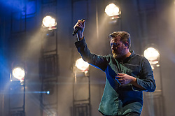 © Licensed to London News Pictures. 16/04/2014. London, UK.   Elbow performing live at The O2 Arena.   In this picture - Guy Garvey.  Elbow is an English alternative rock band consisting of Guy Garvey (vocals, guitar), Richard Jupp (drums, percussion), Craig Potter (keyboards, piano), Mark Potter (guitar, backing vocals) and Pete Turner (bass guitar, backing vocals).   Photo credit : Richard Isaac/LNP