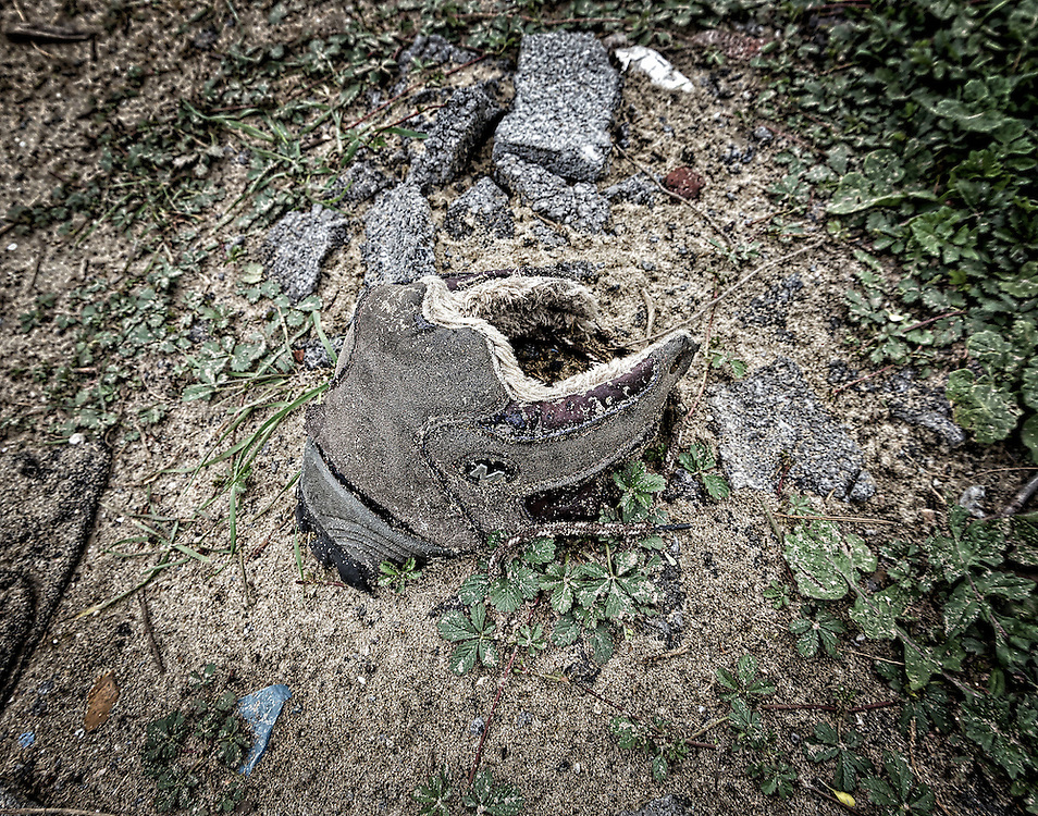 Buried boot. The jungle refugee camp, Calais, France. June 2016 Abandoned boots and shoes left behind as a reminder of the refugee crisis.