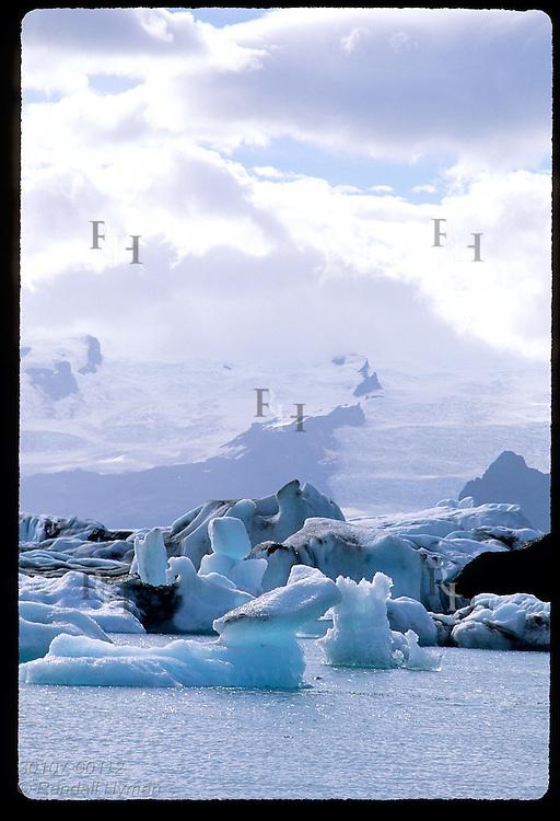 Ice that has calved from Breidamerkurjokull glacier floats in Jokulsarlon (Glacier Lagoon) beneath distant Vatnajokull glacier; SE Iceland.