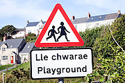 Red triangle playground sign in English and Welsh