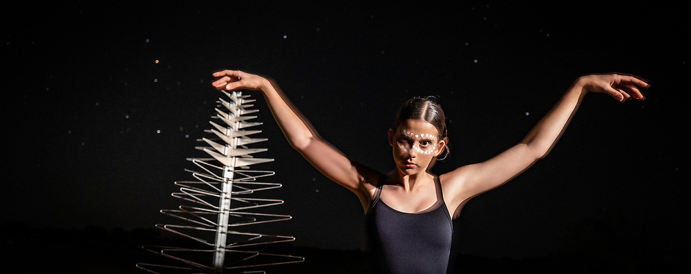Indigenous dancer Lucia Richardson (13) with one of the SKA's low frequency aperture array antennas in the Murchison region of Western Australia