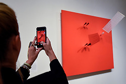 "© Licensed to London News Pictures. 02/07/2019. LONDON, UK.  A visitor views ""Magnetic Wall 9 (Red)"", 1961, by Takis. Preview of a new display by the Greek sculptor Takis at Tate Modern.  The retrospective features over 80 works in Takis' largest exhibition in the UK to date and combines works involving magnetism, light and sound.  The show runs 3 July to 27 October.  Photo credit: Stephen Chung/LNP"