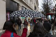 Shoppers carry an umbrella with the words love rainy days outside the Selfridges department store on Oxford Street, on 4th March 2019, in London England.