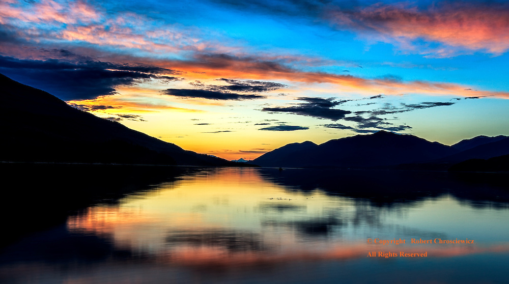 McDonald Creek Sunset: Summer and the sun slowly sets beyond the silhouetted mountains that ring about Upper Arrow Lake, reflecting the magnificently coloured sunset, McDonald Creek Provincial Park, Nakusp British Columbia Canada.