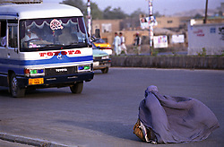 Afghan woman wearing a burqa, walking on the street of Kart-i-Naw. A passenger bus pass by.